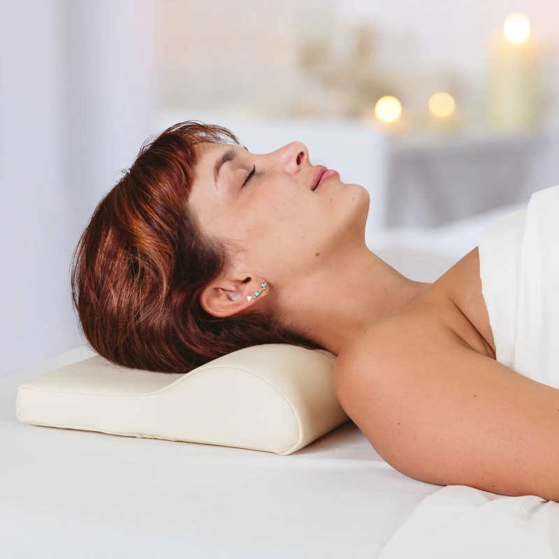 Earthlite Neck Contour Bolster massage pillow shown in use, under the head on a massage table.
